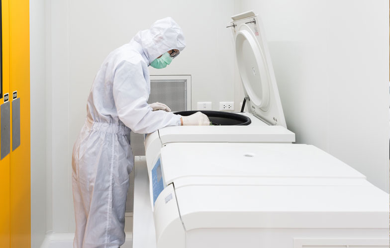 Lab worker in suit looking into large equipment