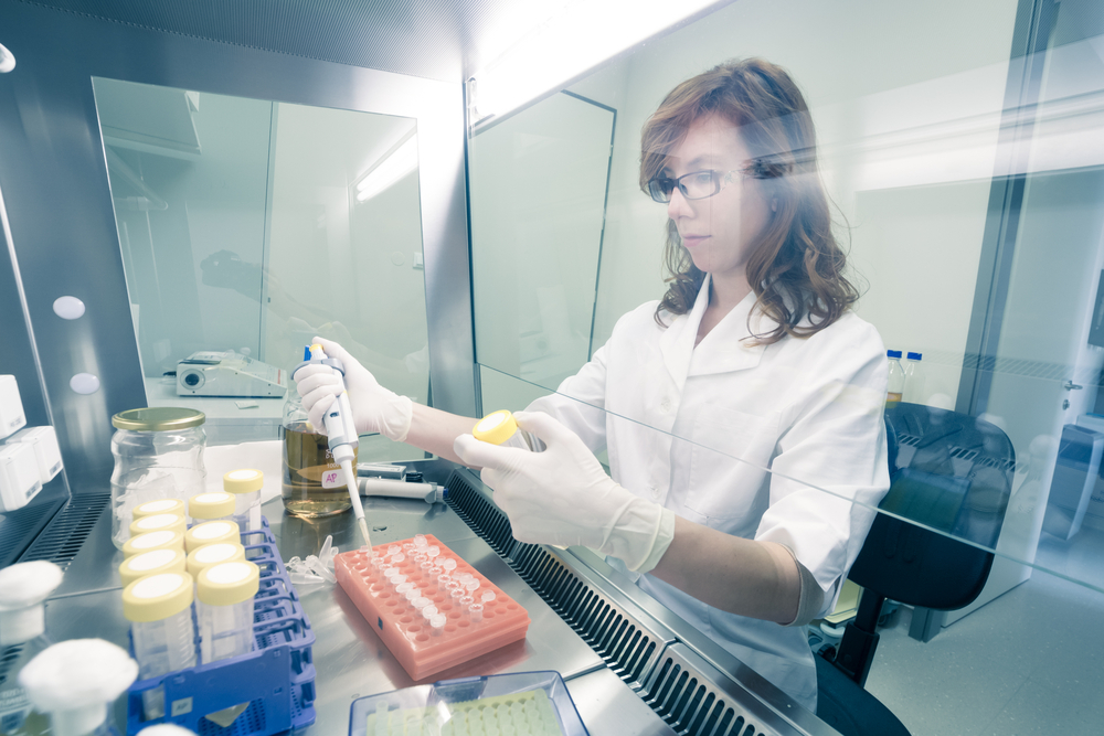 Female life scientist researching in laboratory, pipetting cell culture medium samples in laminar flow. Photo taken from laminar interior