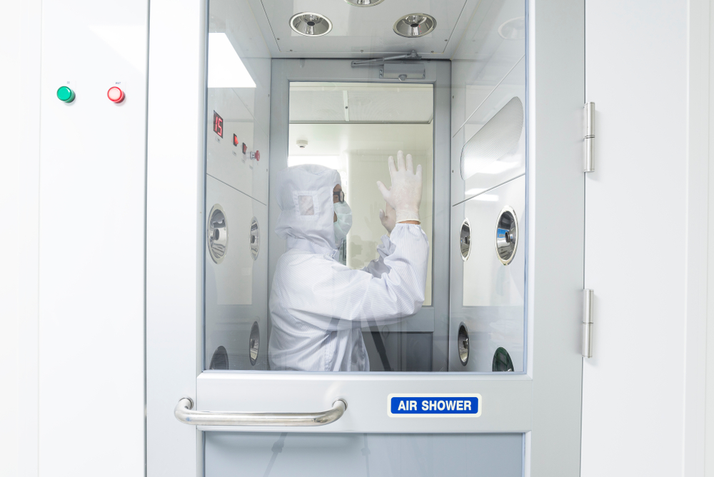 A scientist in sterile coverall gown using air shower to remove particle contamination before going to work area, cleanroom